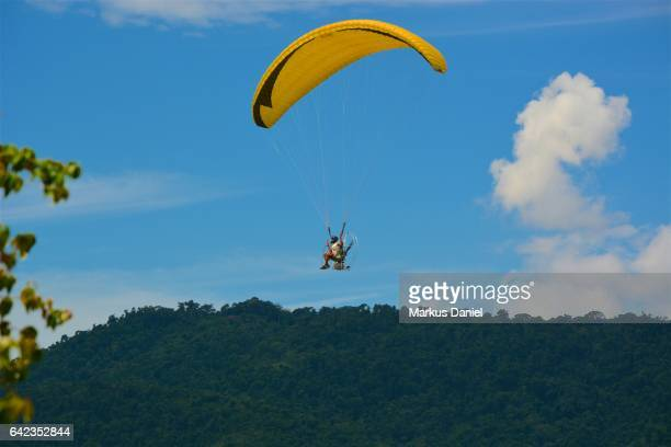 One paraglider with green coast mountains in the background over the bay of Paraty, Rio de Janeiro