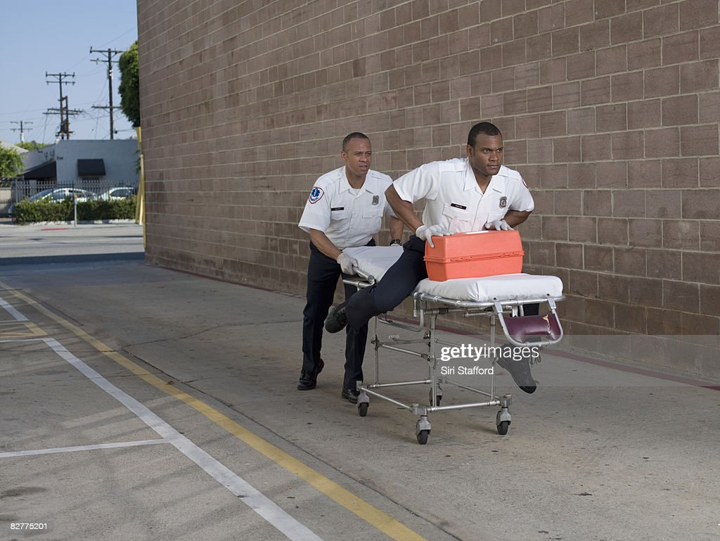 one paramedic pushing another on gurney : Stock Photo