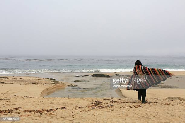 One person on the beach wearing a colorful antique serape. Early morning fog.