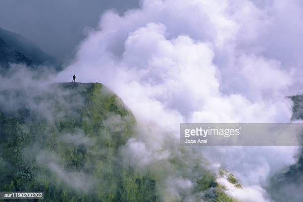 One person standing on the plateau surrounded by smoke due to volcano, Costa Rica.