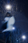 Blurry young woman walking alone in snowy and windy city streets in winter night , low angle view