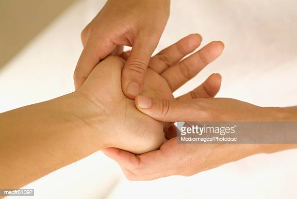 One person's hand inside another's, with fingers pressing on palm