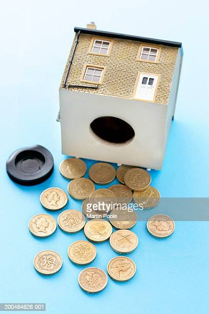 One pound coins tipped out from money box in form of house