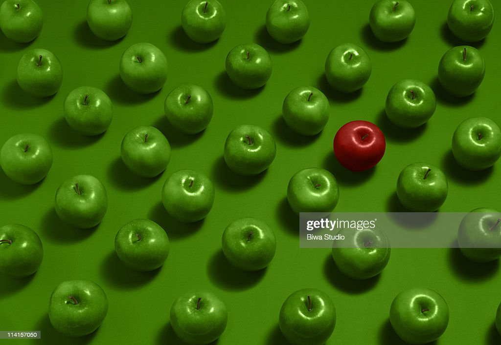 One red apple with many green apples : Stock Photo