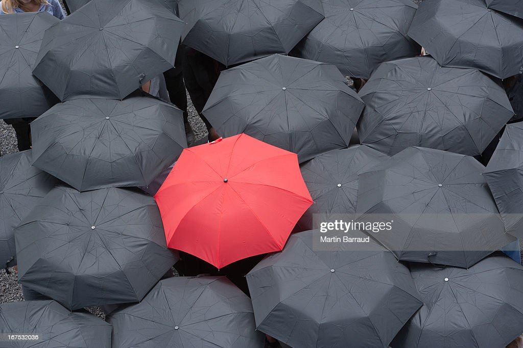 One red umbrella at center of multiple black umbrellas : Stock Photo