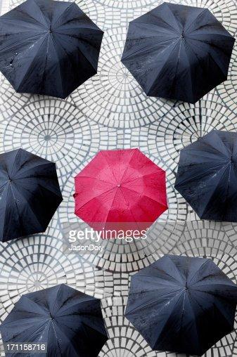 One red umbrella encircled by black umbrellas