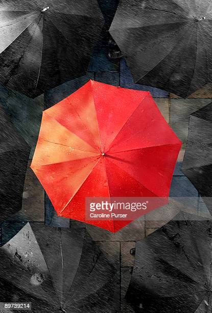 One red umbrella surrounded by black umbrellas