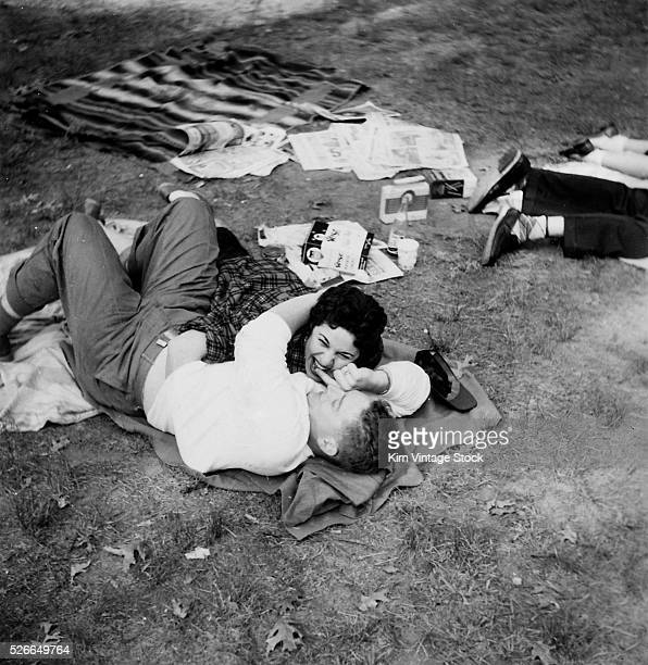 One romantic couple embraces on a blanket while another couple lay together out of the frame on picnic