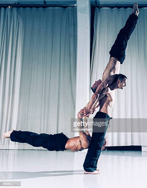 One strong acrobat holds two other men above the ground