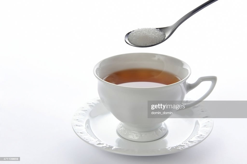 One tea spoon of sugar above china cup of tea
