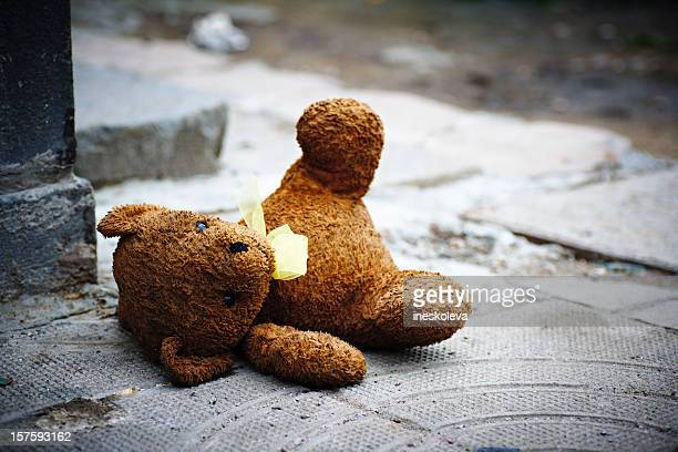 One teddy bear laying in the ground