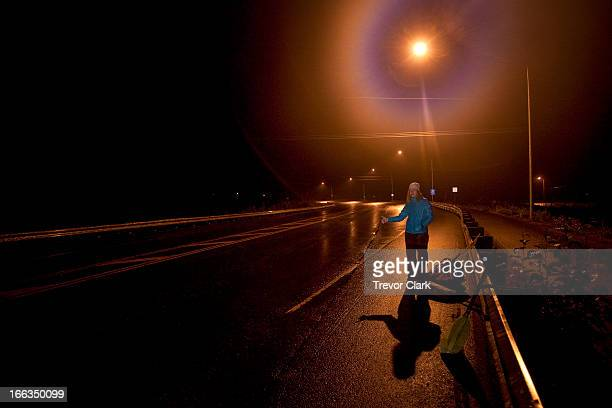 One woman hitch hiking at night under a street light.