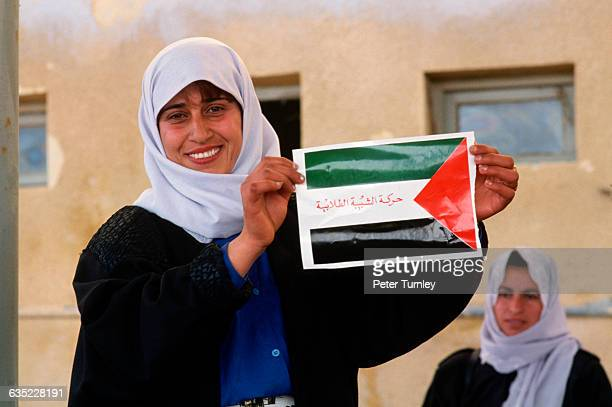One woman holds a Palestinian flag while another stands behind her