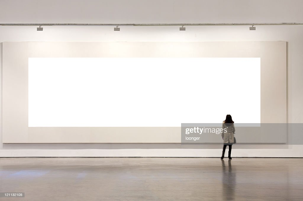 One woman looking at white frame in an art gallery : Stock Photo