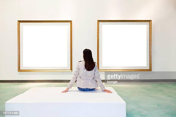 Eine Frau, die auf weißen Rahmen in Kunstgalerie