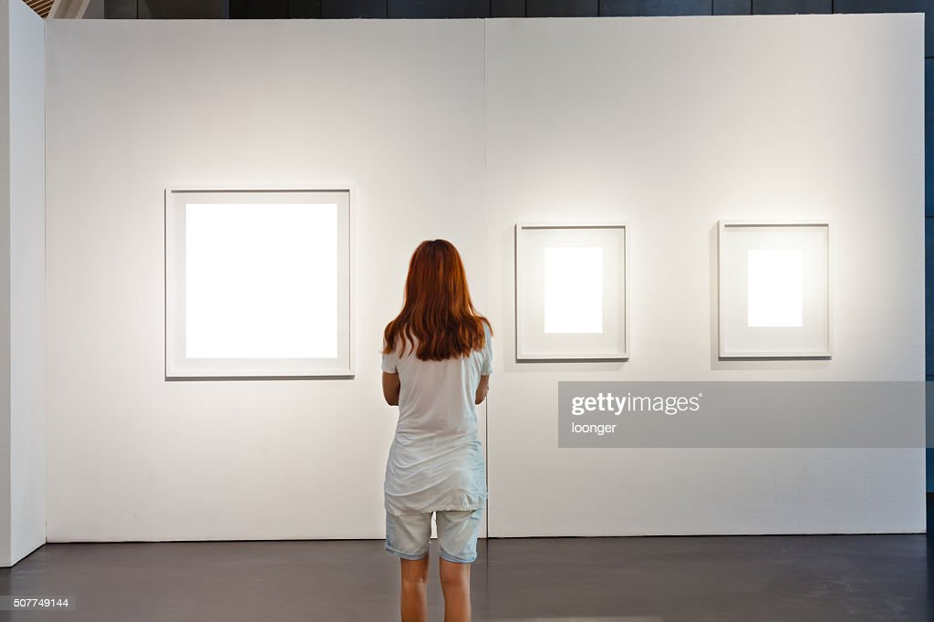 One woman looking at white frames in an art gallery : Stock Photo