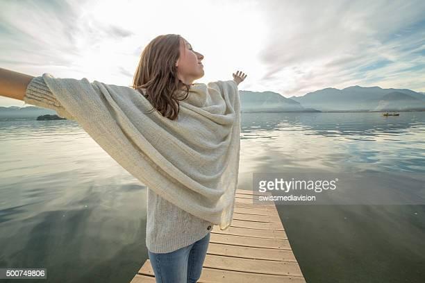 Eine Frau steht am pier Ausgestreckte Arme, entspannt