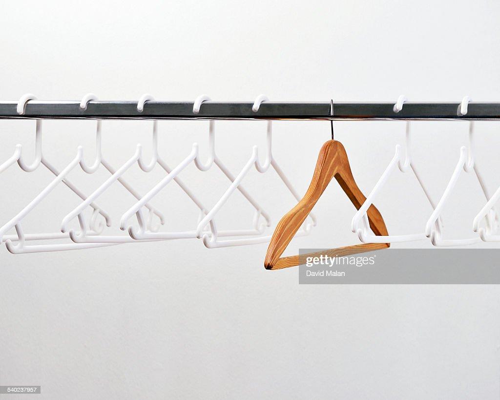 One wooden coat hanger amongst plastic hangers