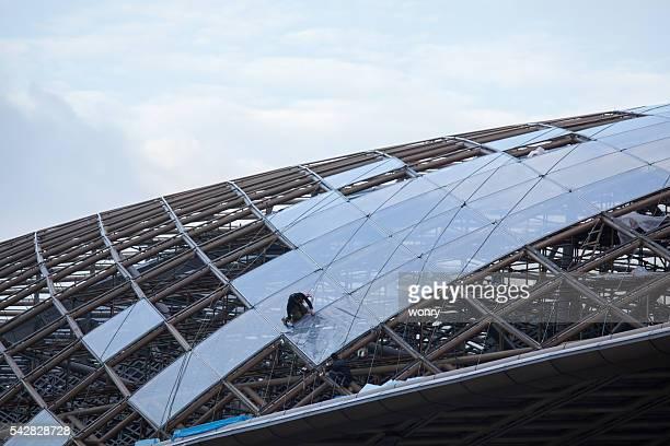 Un travailleur sur le toit de bâtiment moderne.