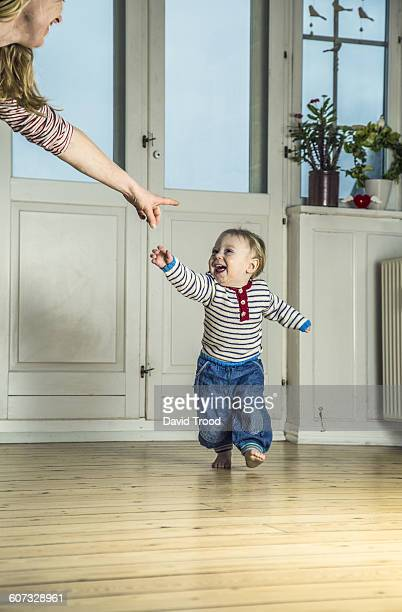 One year old boy learning to walk