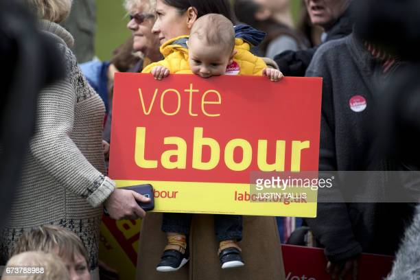 One yearold angelo nibbles on a placard as Labour supporters wait for the arrival of Britain's opposition Labour Party Leader Jeremy Corbyn for a...