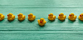 One yellow rubber duck breaking away from a line of orderly yellow rubber ducks moving in a straight direction on a turquoise colored wooden table background conceptually representing water. Concept i