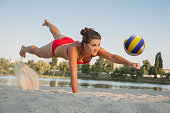 one young beautiful lady is playing volleyball on the beach, professional fly, summer time on beach. sport activity with red bikini making a save.