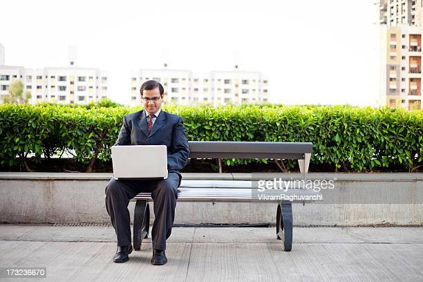One Young Confident Indian Corporate Businessman Using Laptop Outdoors