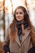 one young girl, looking away, listening to headphones, winter autumn coat, upper body shot.