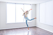 One young happy woman jumping up in empty modern new room with hardwood floors and large sunny windows in apartment