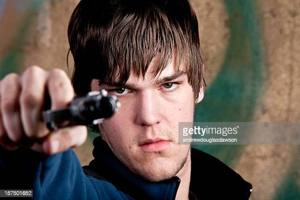 One young man aiming gun at camera