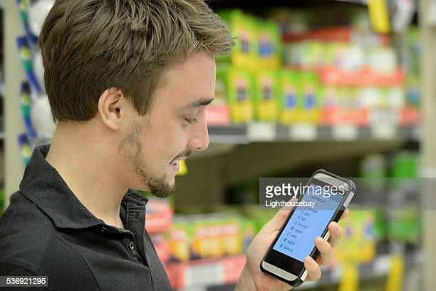 One young man shopping in supermarket using a cell phone