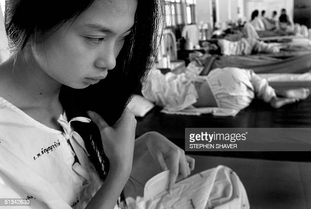 One young Thai girl combs her hair as others most experiencing varying degrees of mental pyschosis from withdrawal and medication sit and sleep on...