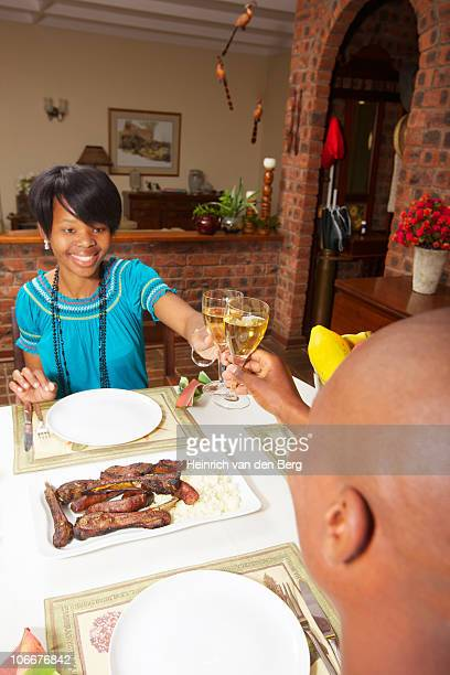 One young woman and man toasting before they eat their meal, KwaZulu-Natal, South Africa