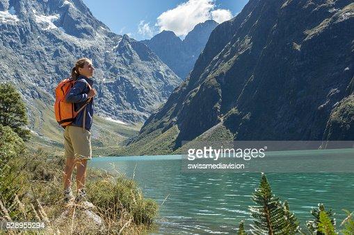 One young woman hiking, reaches mountain lake