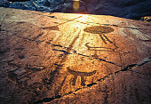 Fragment of Onega petroglyphs on a granite plate at sunset. Age of object - 5000-6000 years. Russia, Karelia.