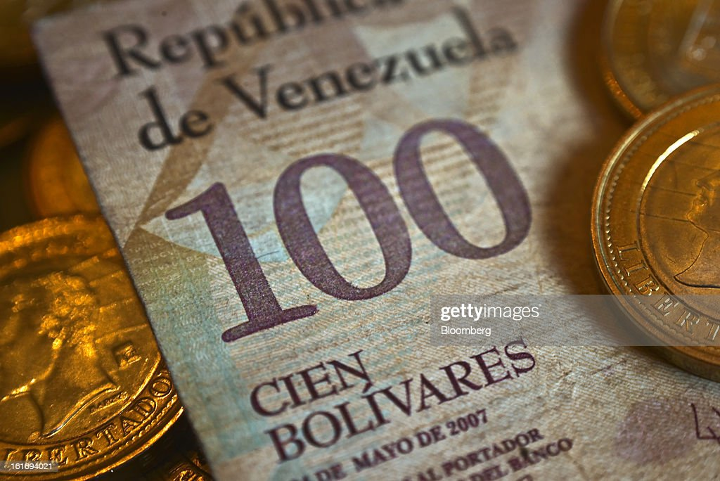 A one-hundred bolivar note is arranged for a photograph with bolivar coins in Caracas, Venezuela, on Wednesday, Feb. 13, 2013. Venezuelan President Hugo Chavez, who hasn't been seen or heard from publicly since arriving in Havana on Dec. 10 for cancer surgery, ordered his government to weaken the exchange rate by 32 percent to 6.3 bolivars per dollar starting on Feb. 13. Photographer: Meridith Kohut/Bloomberg via Getty Images