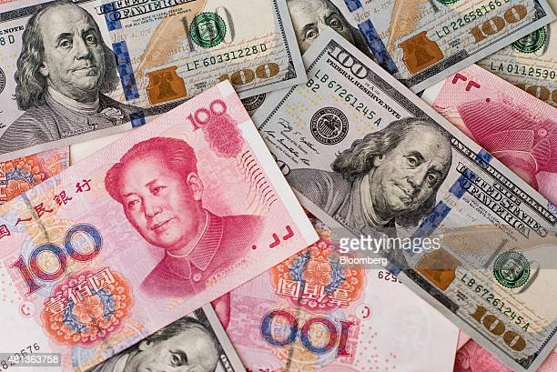 US onehundred dollar bills and Chinese onehundred yuan banknotes are arranged for a photograph in Hong Kong China on Monday July 20 2015 The yuan has...