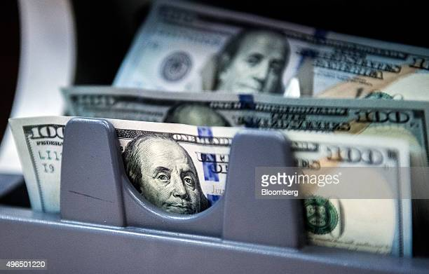 US onehundred dollar currency banknotes pass through a money counting machine at a bank branch inside the FHB Commercial Bank Ltd also known as FHB...