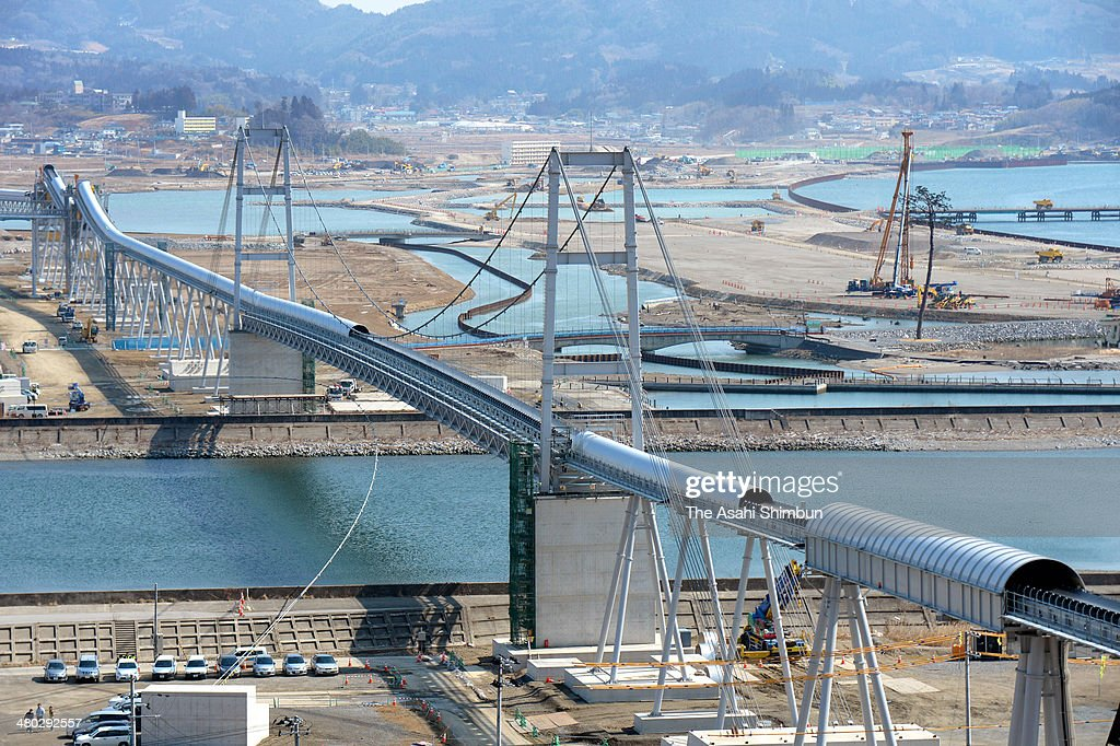 One-kilometer-long belt conveyer starts operation on March 24, 2014 in Rikuzentakata, Iwate, Japan. The 1.8-meter-wide conveyer, connects a 120-meter-high hill and tsunami devastated city center, enables to carry 20,000 cubic meters soil per day. While creating a new residential area on the top of the hill by lowering the hight to 50 meters, approximately 860 million cubic meters soil are reused to fill the city center to bank, raise the land level.