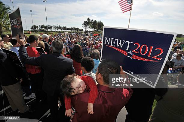 Oneyearold Anaiah Caraballo sleeps on her father Benjamin Caraballo's shoulder as Republican presidential hopeful Newt Gingrich speaks at the the PGA...