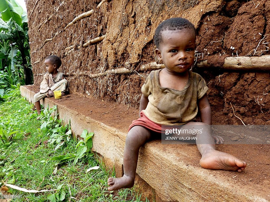 Oneyearold Ejigayehu who suffers from malnutrition after her family's maize crop failed this year because of delayed rains sits next to the mud hut...