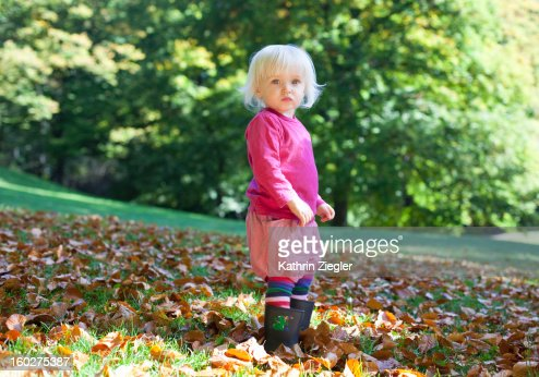 one-year-old girl standing in autumn foliage : Stock Photo