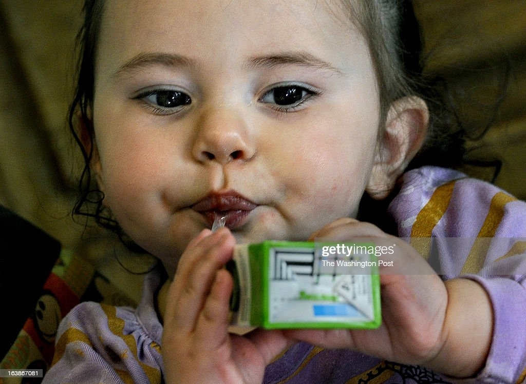 One-year-old Jaeliece Ortiz enjoys some of the food (fruit juice) her mother (Rebecka Ortiz) just brought home after shopping with her SNAP (food stamps) card. Many families and individuals in Woonsocket, Rhode Island are needy and take part in the SNAP (food stamps) program. Photo by Michael S. Williamson/The Washington Post via Getty Images