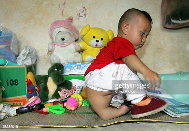Oneyearold Wei Wei a young child with three legs and both female male reproductive organs plays on a bed at the Dongzhimen Hospital on August 29 2005...