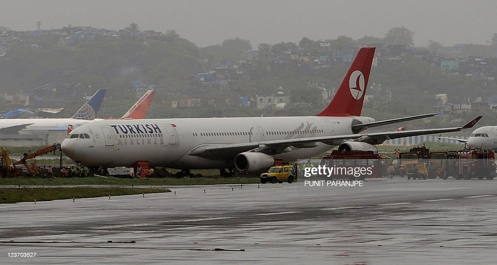 Ongoing recovery operations to move a Turkish Airlines Airbus A340 aircraft, which skidded off a taxiway September 2, is seen at the Mumbai Airport on September 4, 2011. The main runway of the international airport in Mumbai remained shut as incessant rains hampered the towing of a Turkish Airlines plane stuck in mud near the taxiway since September 2, officials said. AFP PHOTO/ Punit PARANJPE
