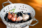 Onion garlic with  young green plumule on Black marble in white steel bowl.