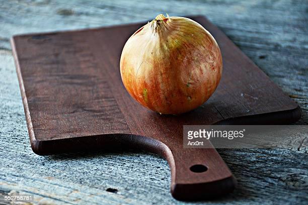 Onion on wooden chopping board