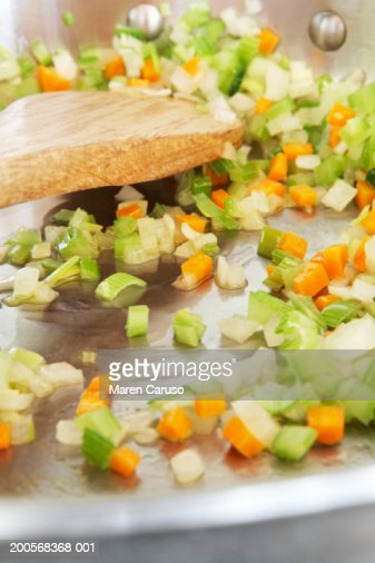 Onions, celery and carrots being sauteed in frying pan