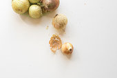 High angle view of natural looking brown onions on white table and in bag (selective focus)